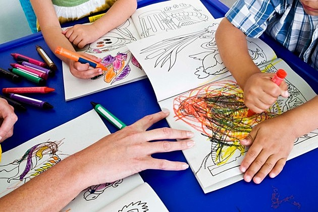 Students coloring and adult stopping the scribbling